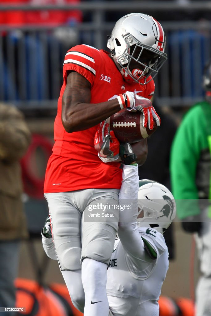 Binjimen Victor #9 of the Ohio State Buckeyes makes the catch on a 48-yard touchdown pass in the third quarter over Justin Layne #2 of the Michigan State Spartans at Ohio Stadium on November 11, 2017 in Columbus, Ohio. Ohio State defeated Michigan State 48-3.