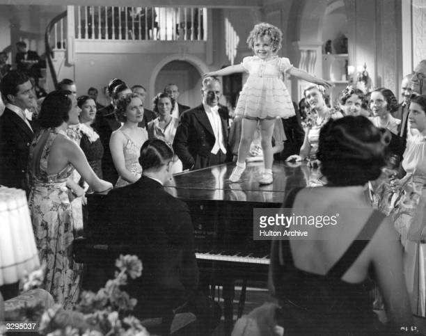 Binkie Stuart a Shirley Temple doppleganger tap dances on a piano top to an admiring crowd in 'Little Miss Somebody' The film was directed by Walter...