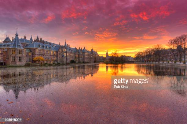 binnnenhof and het torentje reflected in the hofvijver and a red afterglow in the sky - the hague stock pictures, royalty-free photos & images