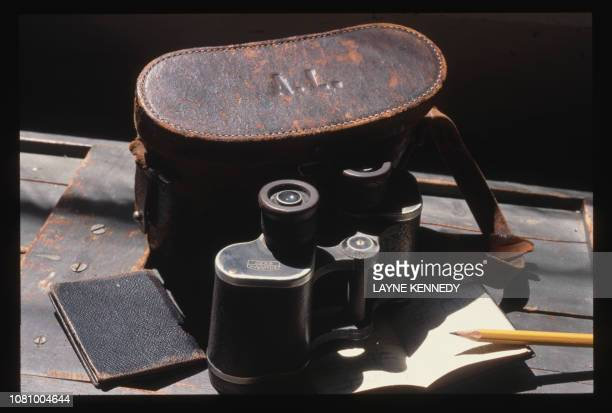 Binoculars and a traveling case sit atop a journal on a table inside the Aldo Leopold cabin The Leopold family cabin was converted from a chicken...