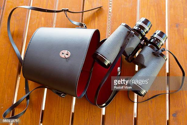 Binoculars with leather case on a wooden table
