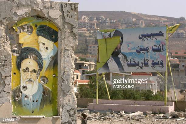A pockmarked mural painting of the late founder of the Islamic republic of Iran Ayatollah Ruhollah Khomeini stands next to a billboard with a ripped...