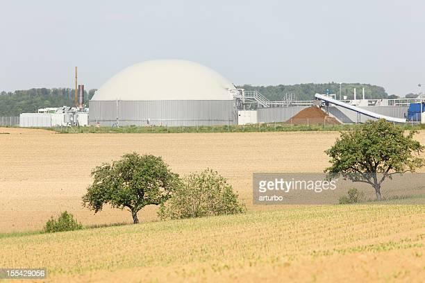 bio gas power generator hinter frischen bepflanzten Feld und Bäume