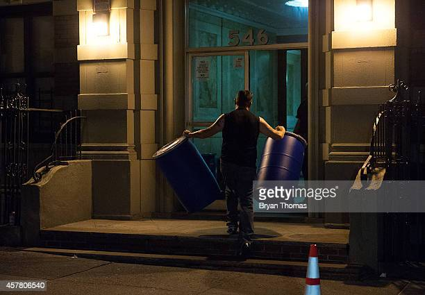 Bio Recovery Corporation employees carry equipment into 546 West 147th Street October 24 2014 in New York City After returning to New York City from...
