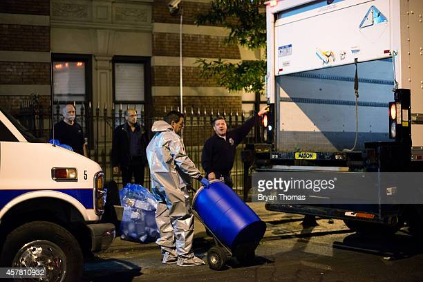 Bio Recovery Corporation employees hand over potentially contaminated materials to the CDC outside of 546 West 147th Street October 24 2014 in New...