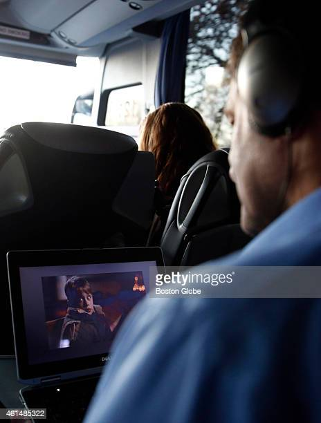 Biogen Idec Engineer Bob Pascucci of Marlborough watches the movie 'Home Alone' on his laptop aboard the Biogen Bus that shuttles employees between...