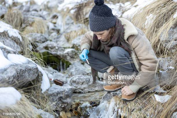 biologist at work conducting the alkaline test of mountain springs water sources - acid rain stock pictures, royalty-free photos & images