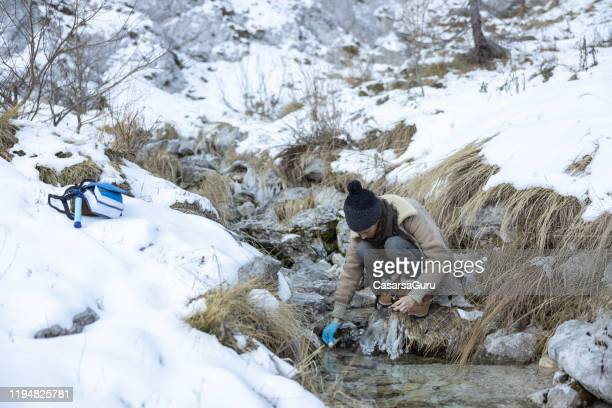 biologist taking an alkaline test of mountain spring water in wintertime - ecologist stock pictures, royalty-free photos & images