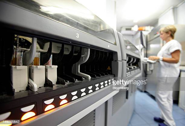 A biologist uses an Architect ci4100 automated analyzer manufactured by Abbott Laboratories to test blood samples in the medical laboratory of the...