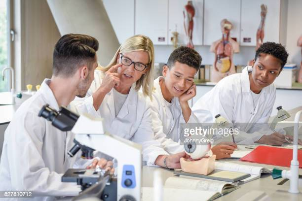 Biology teacher explaining to male student, model of human eye in laboratory
