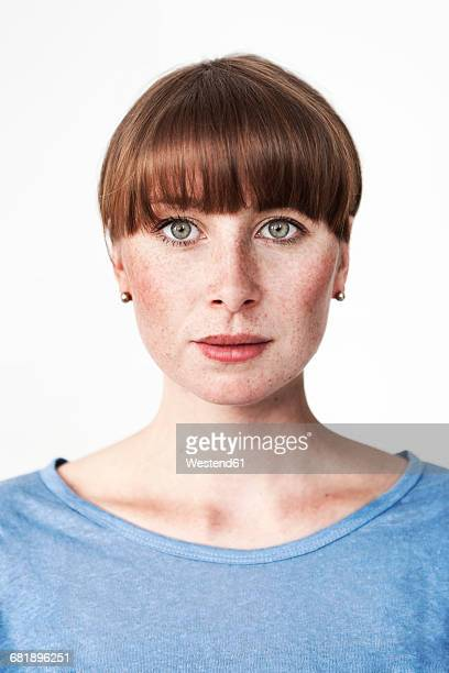 Biometric passport photo of a green-eyed read-haired woman with freckles and bangs