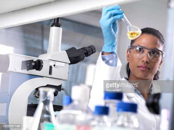 biotechnology research, female scientist mixing a chemical formula - 科学者 ストックフォトと画像
