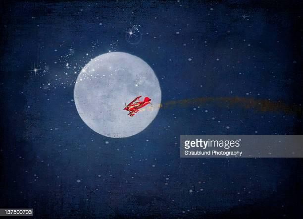 biplane crossing full moon - doppeldecker flugzeug stock-fotos und bilder