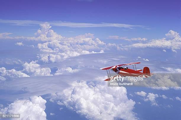 biplane flying above the clouds - doppeldecker flugzeug stock-fotos und bilder
