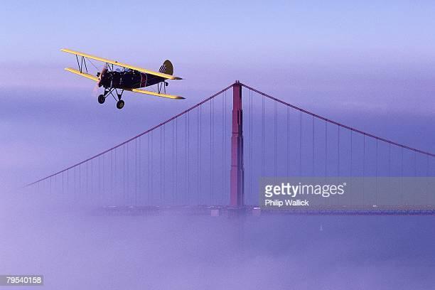 biplane flying over golden gate bridge - doppeldecker flugzeug stock-fotos und bilder
