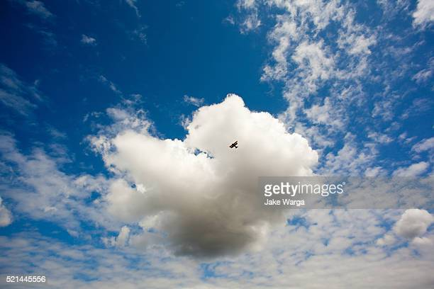 bi-plane in front of cloud - jake warga stock pictures, royalty-free photos & images