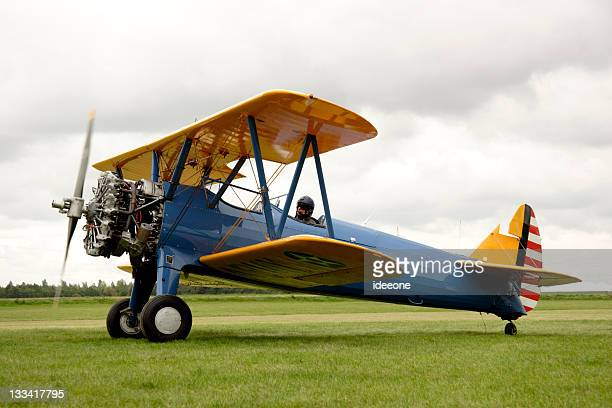 Biplane starting up its engines in a field