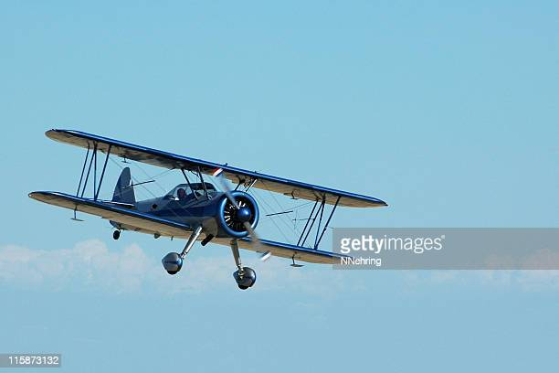 biplane stearman kadet flying in sky - private aeroplane stock pictures, royalty-free photos & images