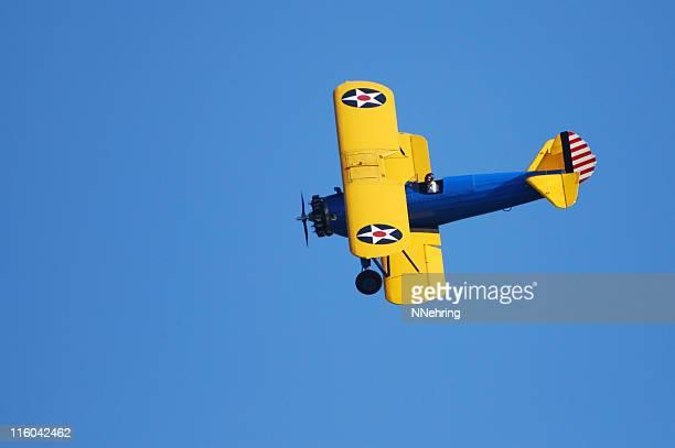 WWII biplane Stearman PT17 Kaydet flying in clear blue sky