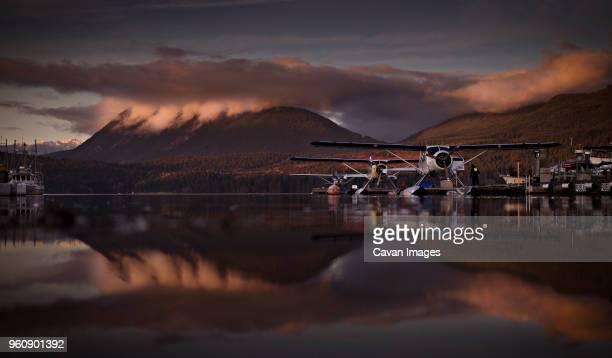 biplanes parked in lake against mountain during sunset - doppeldecker flugzeug stock-fotos und bilder