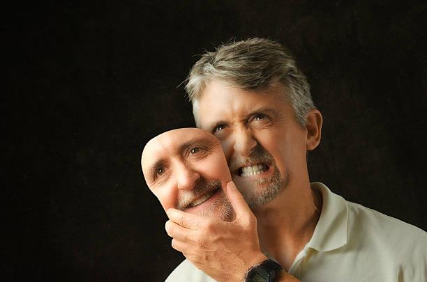 Bipolar disorder angry emotional man with fake smile mask