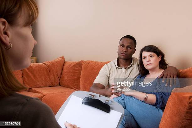 Bi-racial couple on the couch looking at consultant or therapist