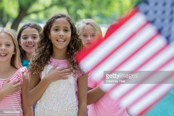 biracial elementary age little girl reciting pledge of allegiance with classmates outdoors - flag day stock pictures, royalty-free photos & images