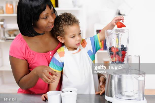 Biracial Toddler Helping His Mother Preparing A Smoothie