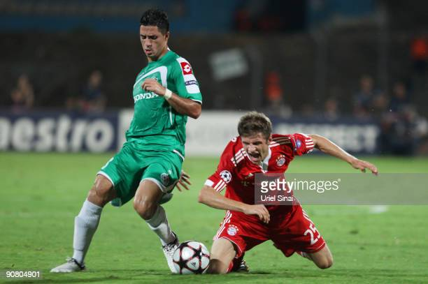 Biram Kayal of Maccabi Haifa and Thomas Muller of FC Bayern Muenchen fight for possession during the UEFA Champions League Group A match between...