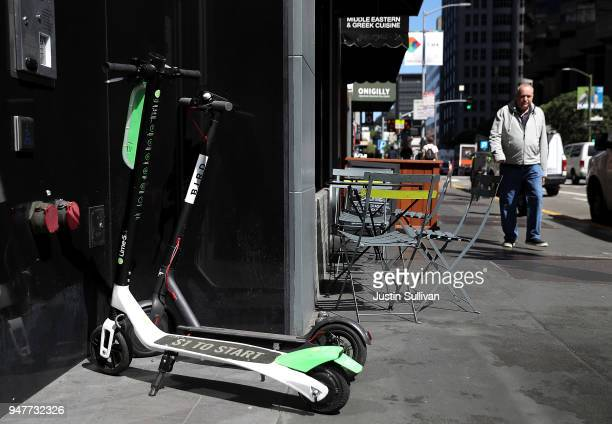 Bird and Lime scooters sit parked in front of a building on April 17 2018 in San Francisco California Three weeks after three companies started...