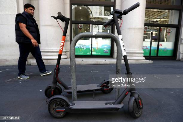 Bird and Spin scooters sit parked on a street corner on April 17 2018 in San Francisco California Three weeks after three companies started placing...