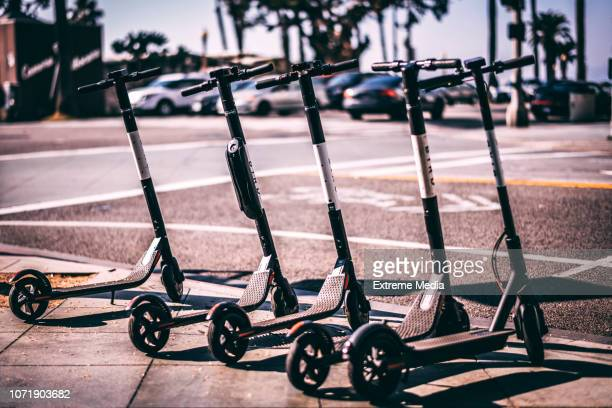 bird electric scooters parked in a row on a sidewalk - mobility scooter stock photos and pictures