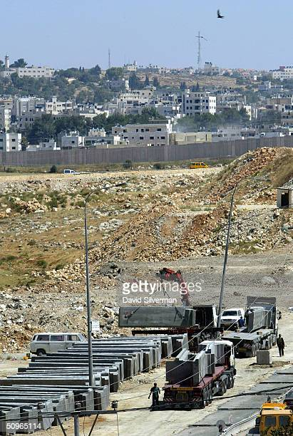 A'RAM WEST BANK JUNE 16 A bird flies overhead as 9meterhigh concrete barriers are delivered to the site where Israel is building its separation...
