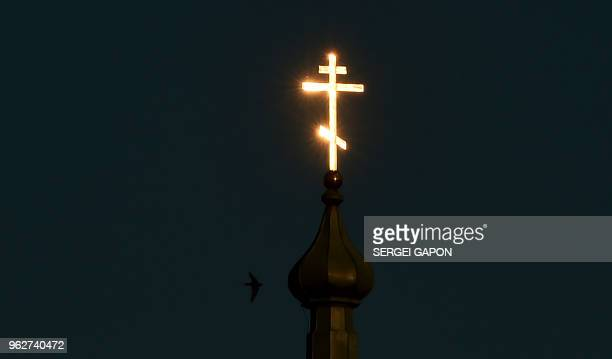 TOPSHOT A bird flies past the cross on the Orthodox Church reflecting sunlight during sunset in the village of Krevo some 100 km northwest of Minsk...