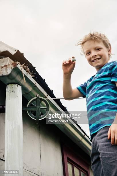"""nido de pájaro en el cobertizo, pequeño muchacho mostrando orgullosamente un huevo. - """"martine doucet"""" or martinedoucet fotografías e imágenes de stock"""