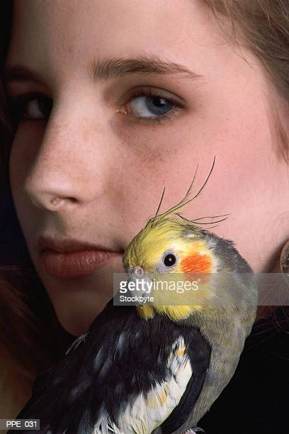 bird on girl's shoulder - cockatiel stock pictures, royalty-free photos & images