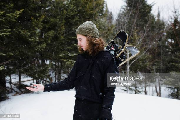 A bird resting on the hand of a young man during winter activity
