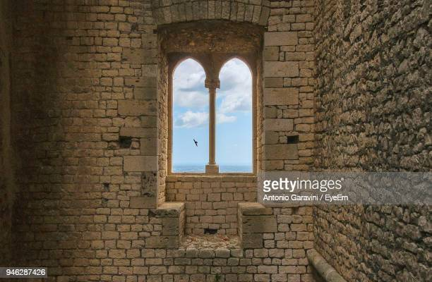 bird seen through window of castle - boog architectonisch element stockfoto's en -beelden