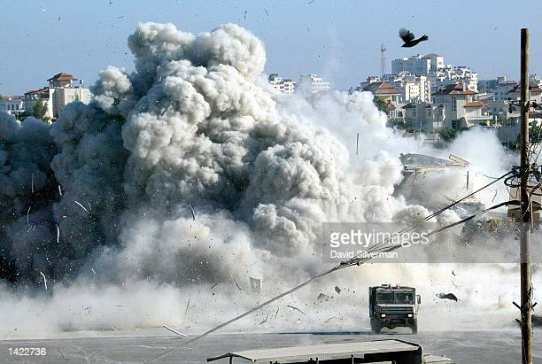 Bird takes flight as a large explosion rocks Palestinian leader Yasser Arafat's headquarters in the West Bank town of Ramallah moments after Israeli...