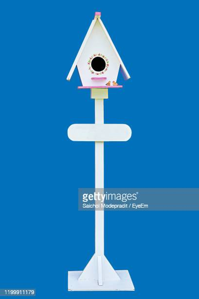 birdhouse on white pole against blue background - pole stock pictures, royalty-free photos & images