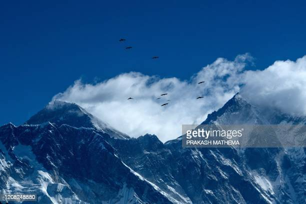 Birds are pictured flying over the Himalayan mountain Mount Everest and other mounts ranges from Namche Bazar in the Everest region, some 140 kms...