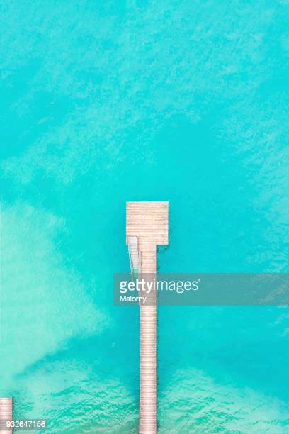 Bird's eye view, aerial view or drone view of a wooden jetty or pier. Turquoise water.