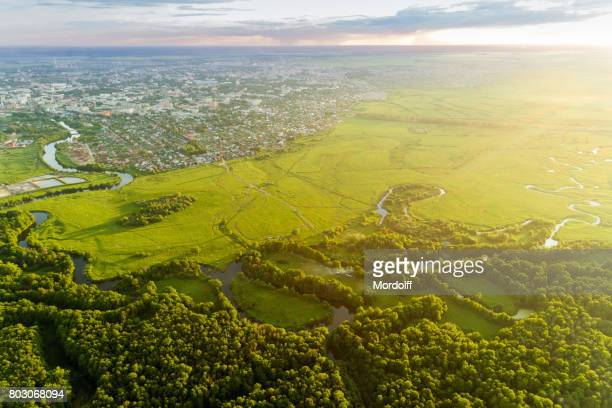 bird's eye view. idyllic rural landscape near town - grove stock photos and pictures
