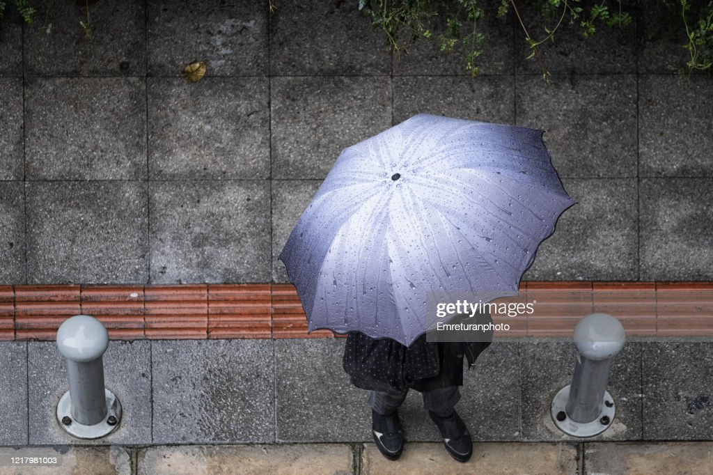 Birds eye view of a person with umbrella under rain : Stock Photo