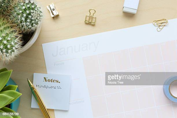 A birds eye view of a table with a calender on it.