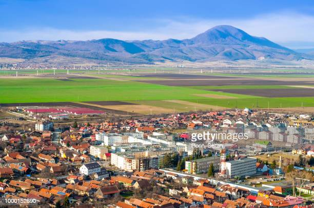 bird's eye view of city in romania with green fields and hills i - florin seitan stock pictures, royalty-free photos & images