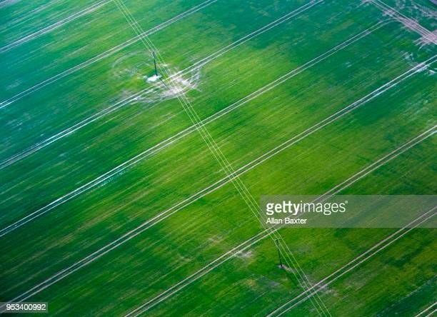 Birds eye view of green fields and pylons in Cambridgeshire