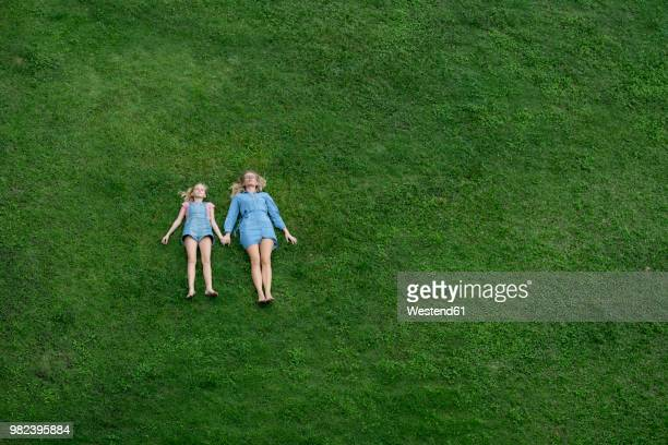 bird's eye view of mother and daughter lying in garden holding hands - lying on back photos stock pictures, royalty-free photos & images