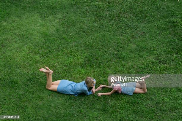 bird's eye view of mother and daughter talking to each other in garden - lying on front stock pictures, royalty-free photos & images