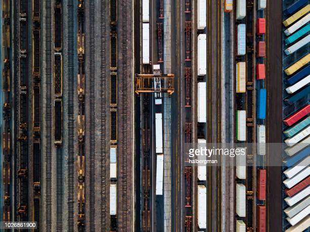 Birds Eye View of Shipping Containers Waiting Beside Freight Train